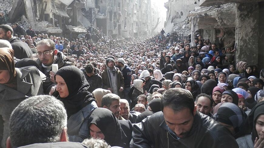 Residents wait to receive food aid distributed by the U.N. Relief and Works Agency (UNRWA) at the besieged al-Yarmouk camp, south of Damascus on January 31, 2014, in this handout picture made available to Reuters February 26, 2014. World powers have passed a landmark Security Council resolution demanding an end to restrictions on humanitarian operations in Syria, but aid workers doubt it has the punch to make Damascus grant access and let stuck convoys deliver vital supplies. The resolution called for the i