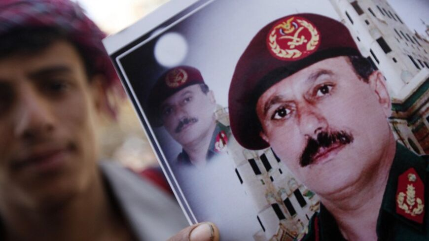 A vendor poses with images of former President Ali Abdullah Saleh (bottom) in Sanaa March 1, 2014. Western diplomats say Saleh and former Vice President Ali Salim Al-Beidh are top candidates of a blacklist by a newly created U.N. sanctions committee for Yemen that will impose asset freezes and travel bans on specific individuals who obstruct the country's political transition or commits human rights violations. REUTERS/Mohamed al-Sayaghi (YEMEN - Tags: SOCIETY POLITICS) - RTR3FUWN