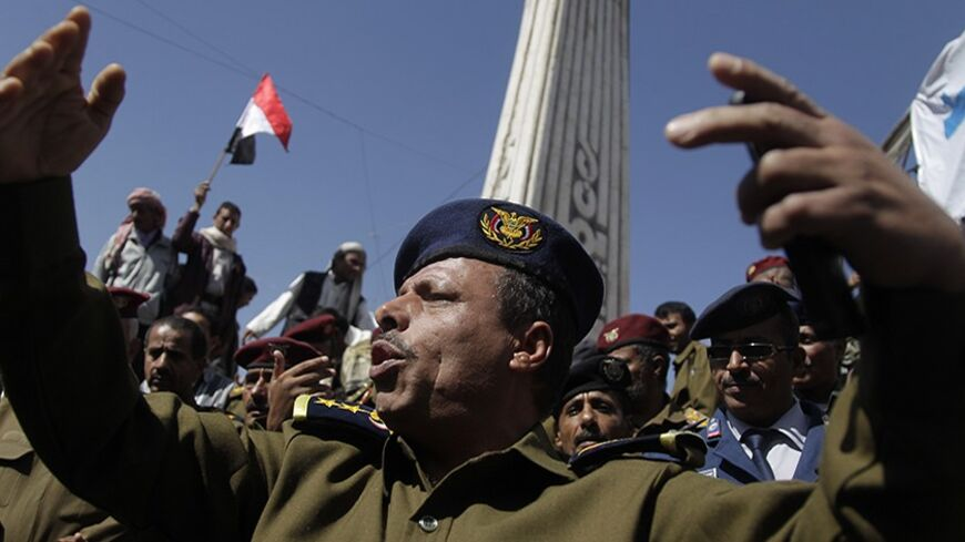 A police officer gestures as he joins other police and army officers during an anti-government demonstration at a Change Square protest camp in Sanaa March 3, 2014. REUTERS/Khaled Abdullah (YEMEN - Tags: POLITICS MILITARY CIVIL UNREST) - RTR3FZGW