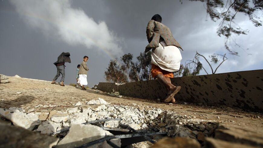 Boys walk on the ruins of their school which was bombed by Shi'ite militants of the Shi'ite al-Houthi group during recent conflicts against local tribes in the Hamdan area west of the Yemeni capital Sanaa March 23, 2014. REUTERS/Mohamed al-Sayaghi (YEMEN - Tags: POLITICS SOCIETY CIVIL UNREST) - RTR3I8RJ