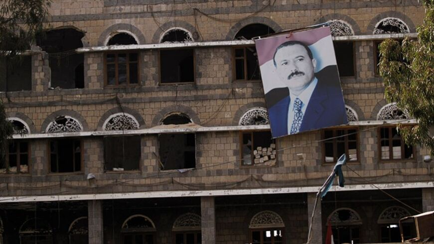 A picture of former Yemeni President Ali Abdullah Saleh hangs on a building of the Standing Committee of the General People's Congress, Saleh's party, in Sanaa, December 17, 2013. The building was damaged during  protests and clashes in 2011. Two years after months of mass protests forced ex-Yemeni President Ali Abdullah Saleh to give up his 33-year rule that brought the country to the brink of civil war, many establishments still bear damages from the conflict. REUTERS/Mohamed al-Sayaghi (YEMEN - Tags: POL