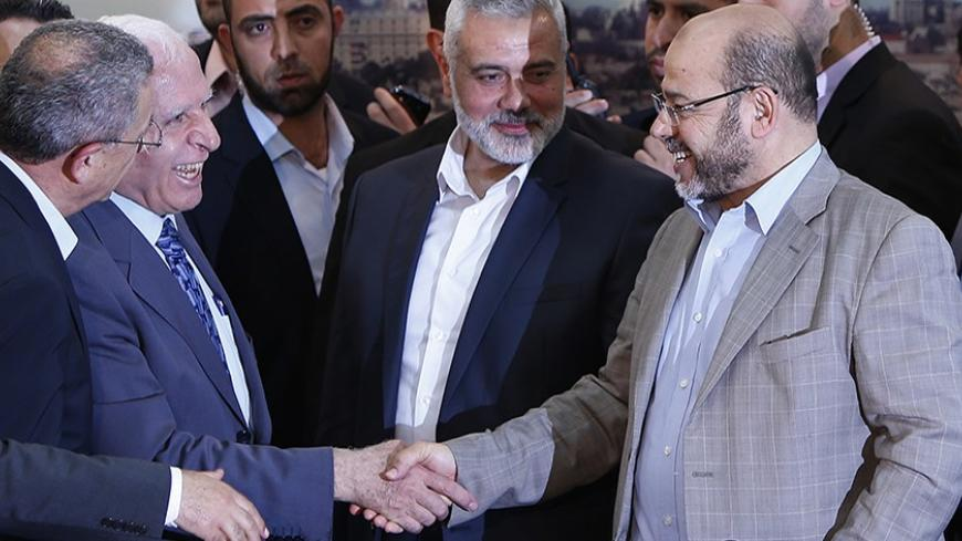 Senior Fatah official Azzam Al-Ahmed (L) shakes hands with senior Hamas leader Moussa Abu Marzouq after announcing a reconciliation agreement in Gaza City April 23, 2014. The Gaza-based Islamist group Hamas and President Mahmoud Abbas's Palestine Liberation Organization (PLO) agreed on Wednesday to implement a unity pact, both sides announced in a joint news conference.REUTERS/Suhaib Salem (GAZA - Tags: POLITICS) - RTR3MBRU