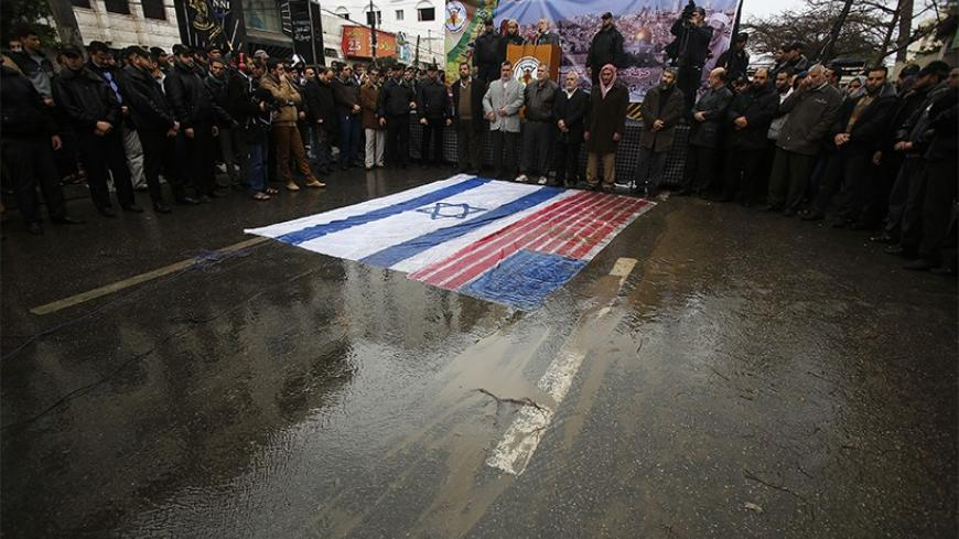Palestinian Islamic Jihad supporters take part in a protest against U.S.-brokered peace talks between Israel and Palestinians as the U.S. and Israel flags are seen on the ground, in Gaza City January 10, 2014. REUTERS/Suhaib Salem (GAZA - Tags: POLITICS CIVIL UNREST) - RTX178KN