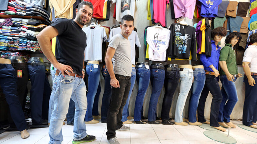 Iranian men pose in a shop selling jeans in Tajrish Bazaar in Tehran on October 7, 2013. A campaign launched by young Iranians on internet networking sites Facebook and Twitter were mocking Israeli President Benjamin Netayahu following his comments during an interview diffused on October 5, in which he implied there is a supposed ban on wearing jeans and listening to Western music in the Islamic Republic. AFP PHOTO/ATTA KENARE        (Photo credit should read ATTA KENARE/AFP/Getty Images)