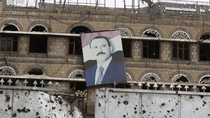 A portrait of Yemen's former president Ali Abdullah Saleh hangs on the wall of the former headquarters of his General People's Congress party in Sanaa May 12, 2014. The building was damaged during the 2011 clashes between forces loyal to Saleh and tribal militias opposing him during the uprising against his rule. REUTERS/Khaled Abdullah (YEMEN - Tags: POLITICS CIVIL UNREST TPX IMAGES OF THE DAY) - RTR3OTK8
