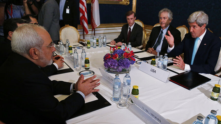 Iran's Foreign Minister Mohammad Javad Zarif (L) meets with U.S. Secretary of State John Kerry (R) at talks between the foreign ministers of the six powers negotiating with Tehran on its nuclear program in Vienna, July 13, 2014.  REUTERS/Jim Bourg    (AUSTRIA - Tags: POLITICS) - RTR3YE8T