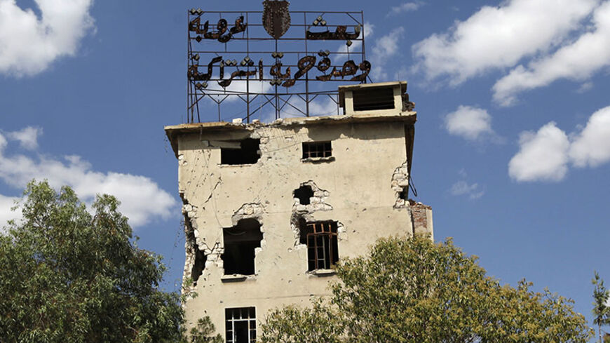 The words: ' Baath, Arabism, Unity, Freedom, Socialism' are seen on top of a damaged building that belongs to forces loyal to Syria's President Bashar al-Assad in Aleppo, June 19, 2013. Picture taken June 19, 2013. REUTERS/Nour Kelze  (SYRIA - Tags: CIVIL UNREST POLITICS CONFLICT) - RTX10UMG