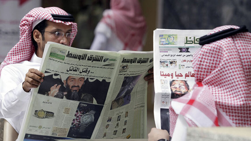 People read the newspapers with cover stories of Osama bin Laden, in Riyadh, May 3, 2011. Bin Laden was killed in a U.S. special forces assault on a Pakistani compound, then quickly buried at sea, in a dramatic end to the long manhunt for the al Qaeda leader who had been the guiding star of global terrorism. REUTERS/Mohammed Mashhor    (SAUDI ARABIA - Tags: SOCIETY MEDIA) - RTR2LXUQ