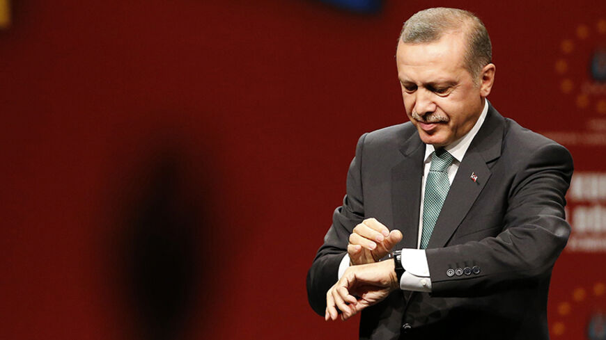 Turkish Prime Minister Tayyip Erdogan looks at his watch at the end of his meeting with supporters during his visit in Cologne May 24, 2014.                 REUTERS/Wolfgang Rattay   (GERMANY - Tags: POLITICS) - RTR3QOIL