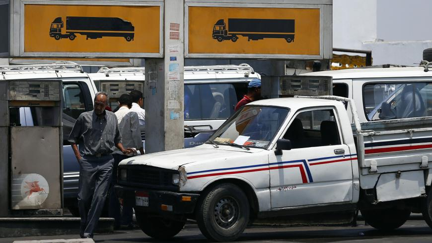 People wait to buy fuel at a petrol station in Cairo July 6, 2014. Egypt's Prime Minister Ibrahim Mehleb has sought to justify politically sensitive subsidy cuts on fuel and natural gas which took effect on Saturday, saying they were a necessary part of fixing an economy hammered by three years of turmoil. Egypt had overnight on Friday slashed its subsidies for car fuel and natural gas, increasing their prices by more than 70 percent. REUTERS/Amr Abdallah Dalsh  (EGYPT - Tags: POLITICS BUSINESS ENERGY TRANS