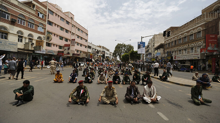 Army and police officers sit on the ground during a protest to denounce fuel prices hikes in Sanaa August 4, 2014. Yemen raised fuel prices last week, oil officials told Reuters, as the impoverished country tries to cut energy subsidies to ease the burden on its budget deficit. REUTERS/Khaled Abdullah (YEMEN - Tags: POLITICS CIVIL UNREST ENERGY MILITARY) - RTR415WW
