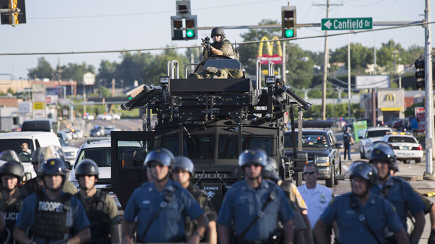 Riot police stand guard as demonstrators protest the shooting death of teenager Michael Brown in Ferguson, Missouri August 13, 2014. Police in Ferguson fired several rounds of tear gas to disperse protesters late on Wednesday, on the fourth night of demonstrations over the fatal shooting last weekend of an unarmed black teenager Brown, 18, by a police officer on Saturday after what police said was a struggle with a gun in a police car. A witness in the case told local media that Brown had raised his arms to
