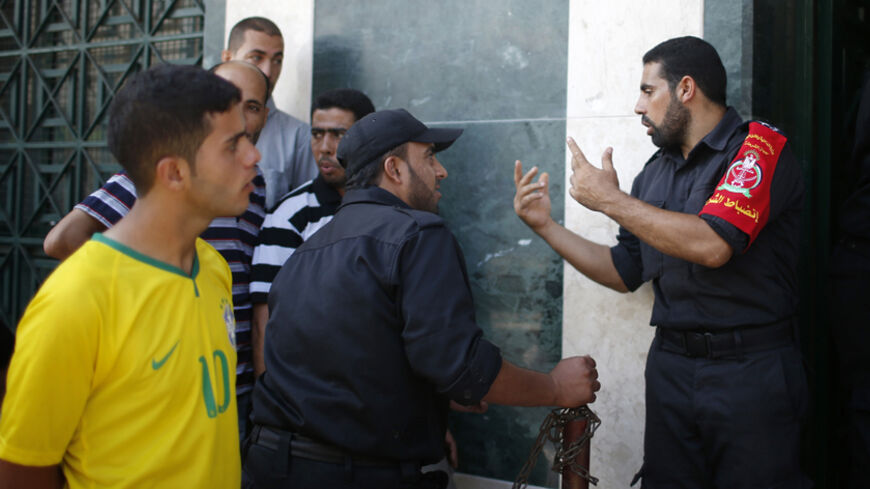 Police officers take charge as Palestinian Hamas-hired employees wait to receive partial payments outside a bank in Gaza City September 11, 2014. Tensions between Fatah and Hamas, the two main Palestinian parties, are close to breaking point over the non-payment of salaries to Gaza's public sector workers, raising the risk of a return to conflict in the territory, officials say. As a stop-gap measure, the Hamas-controlled Finance Ministry in Gaza announced on Wednesday it would make partial payments, betwee
