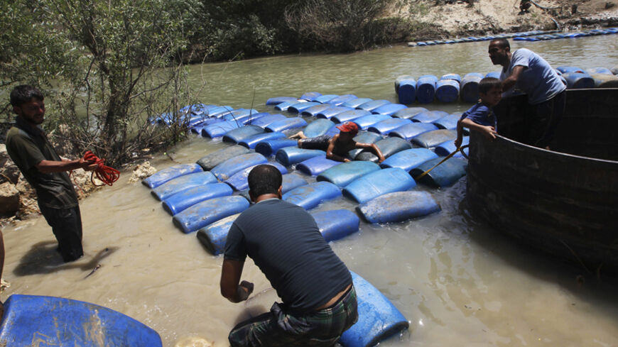 A group of men smuggle diesel fuel from Syria to Turkey hoping to sell it at a higher price, across the Al-Assi River in Darkush town, Idlib countryside May 26, 2013. REUTERS/Muzaffar Salman (SYRIA - Tags: CONFLICT TPX IMAGES OF THE DAY) - RTX1026I