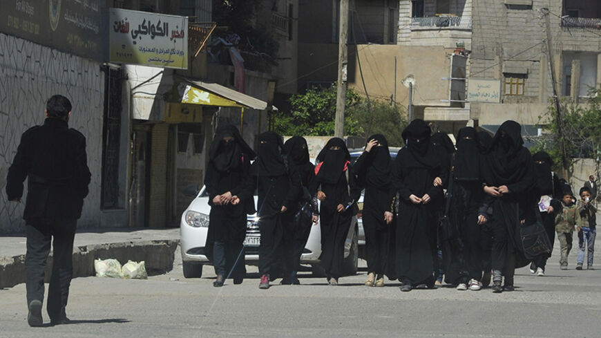 "Female school students wearing a full veil (niqab) walk along a street in the northern province of Raqqa March 31, 2014. The Islamic State in Iraq and the Levant (ISIL) has imposed sweeping restrictions on personal freedoms in the northern province of Raqqa. Among the restrictions, Women must wear the niqab, or full face veil, in public or face unspecified punishments ""in accordance with sharia"", or Islamic law. REUTERS/Stringer   (SYRIA - Tags: POLITICS CIVIL UNREST CONFLICT RELIGION SOCIETY EDUCATION TPX"
