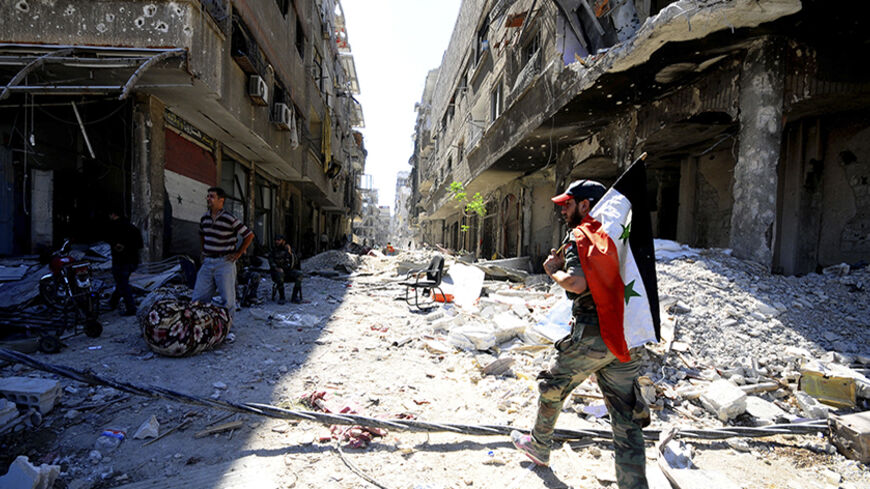 A member of forces loyal to Syria's President Bashar al-Assad holds the Syrian flag as he walks on debris of damaged buildings in al-Dukhaneya neighbourhood near Damascus, after the forces regained control of the area from rebel fighters October 7, 2014. REUTERS/Omar Sanadiki   (SYRIA - Tags: POLITICS CIVIL UNREST CONFLICT) - RTR499FJ