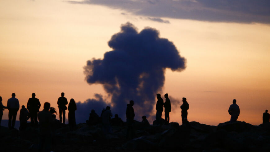 Turkish Kurds watch the smoke rises from Syrian town of Kobani near the Mursitpinar border crossing, on the Turkish-Syrian border in the southeastern town of Suruc in Sanliurfa province, October 18, 2014. A U.S.-led military coalition has been bombing Islamic State fighters who hold a large swathe of territory in both Iraq and Syria, two countries involved in complex multi-sided civil wars in which nearly every country in the Middle East has a stake..    REUTERS/Kai Pfaffenbach (TURKEY  - Tags: MILITARY POL