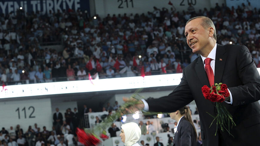 Turkey's Prime Minister Tayyip Erdogan throws flowers to his supporters upon arriving at the Extraordinary Congress of the ruling AK Party (AKP) to choose a new leader of the party, ahead of Erdogan's inauguration as president, in Ankara August 27, 2014. Turkish president-elect Erdogan said on Wednesday he would ask incoming prime minister Ahmet Davutoglu to form a new government on Thursday, and a new cabinet of ministers would be announced the following day.   REUTERS/Rasit Aydogan/Pool  (TURKEY - Tags: P