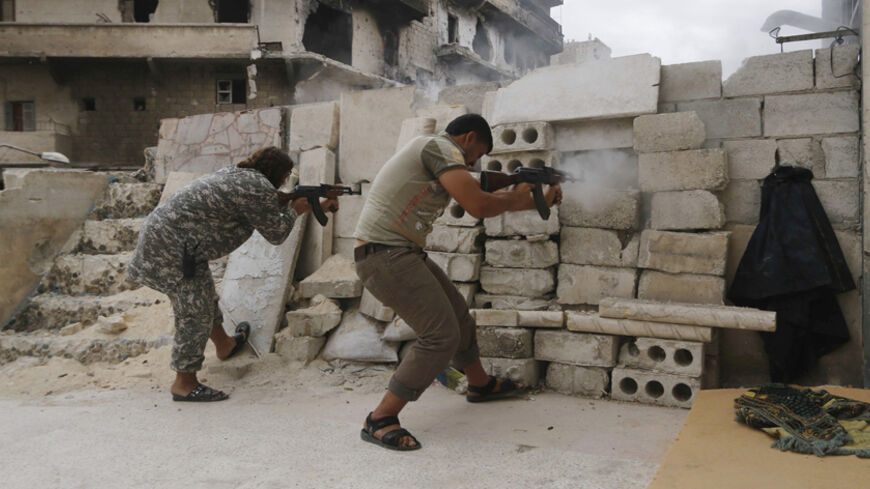 Rebel fighters fire their weapons at the frontline against forces loyal to Syria's President Bashar al-Assad in al-Amriyah neighbourhood of Aleppo October 11, 2014. REUTERS/Hosam Katan    (SYRIA - Tags: POLITICS CIVIL UNREST MILITARY CONFLICT) - RTR49S8W