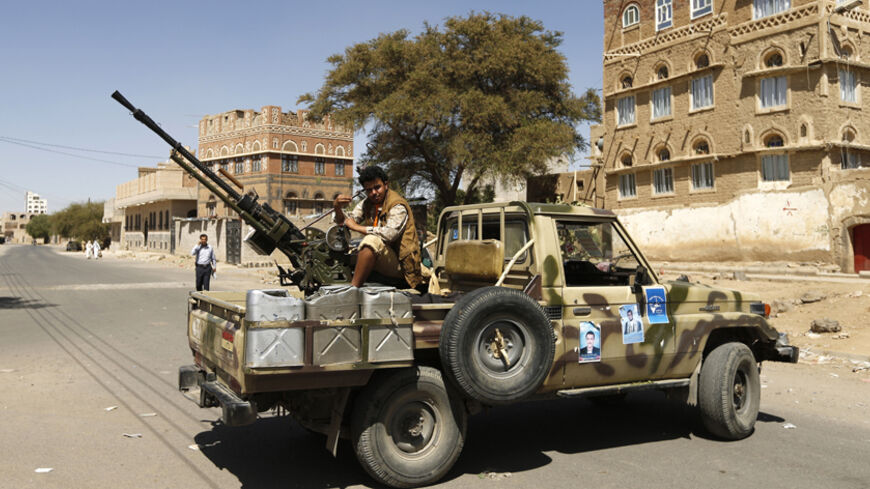 A follower of the Shi'ite Houthi movement mans a machine gun mounted on a military pick up in Sanaa October 20, 2014. The truck was taken by the movement's fighters during recent clashes with army soldiers in Sanaa. REUTERS/Khaled Abdullah (YEMEN - Tags: POLITICS CIVIL UNREST MILITARY) - RTR4AU1L