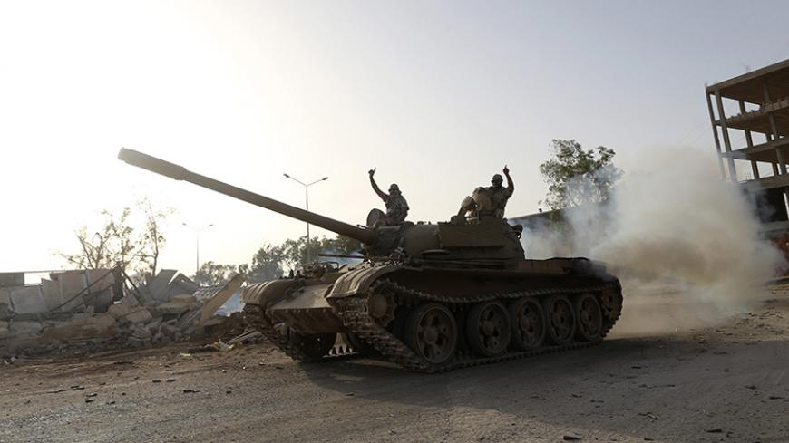 Fighters from the Benghazi Shura Council, which includes former rebels and militants from al Qaeda-linked Ansar al-Sharia, gesture on top of a tank next to the camp of the special forces in Benghazi July 30, 2014. On Wednesday, the eastern city of Benghazi was quieter after Islamist fighters and allied militia forces overran a special forces army base in the city in a major blow to a military campaign against Islamist militants there. The self-declared Benghazi Shura Council forces took over the base on Tue