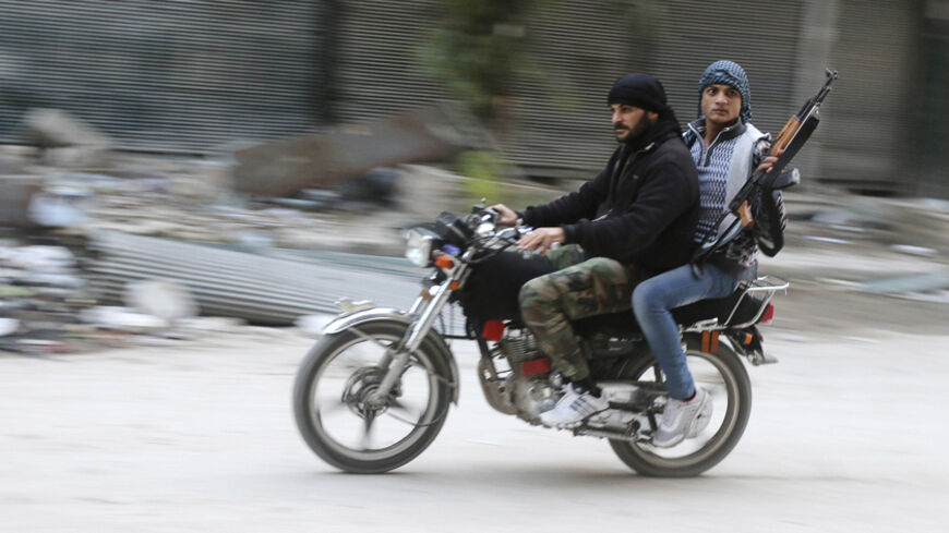 Rebel fighters ride a motorbike in the old city of Aleppo December 7, 2014. Picture taken December 7, 2014. REUTERS/Abdalrhman Ismail (SYRIA - Tags: POLITICS CIVIL UNREST CONFLICT) - RTR4H3I6