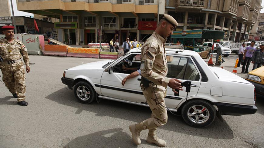 An Iraqi soldier scans a car with a bomb detector a checkpoint at Shurja market in central Baghdad, April 28, 2012.   REUTERS/Thaier al-Sudani (IRAQ - Tags : - Tags: CONFLICT MILITARY) - RTR31CIN