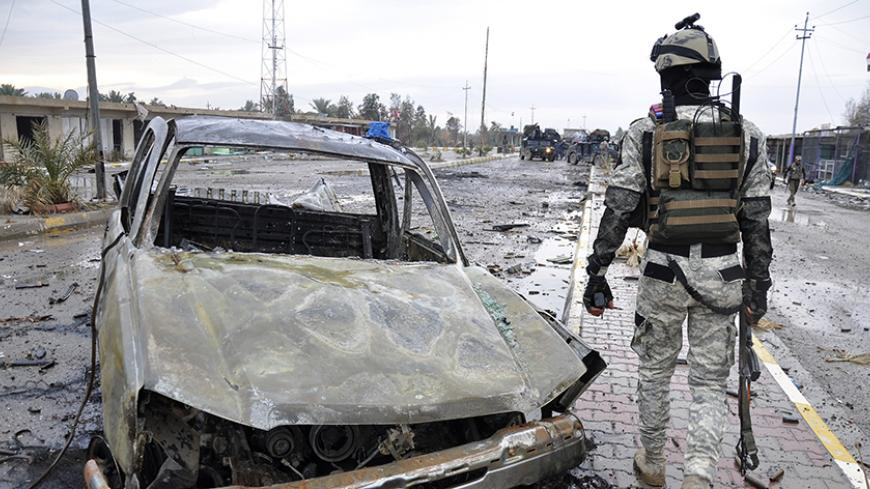 A member of the Iraqi security forces walks past a destroyed vehicle belonging to Islamic State militants during an intensive security deployment on the outskirts of Samarra December 14, 2014. Picture taken December 14, 2014. REUTERS/Stringer (IRAQ - Tags: CIVIL UNREST POLITICS MILITARY) - RTR4I0GG