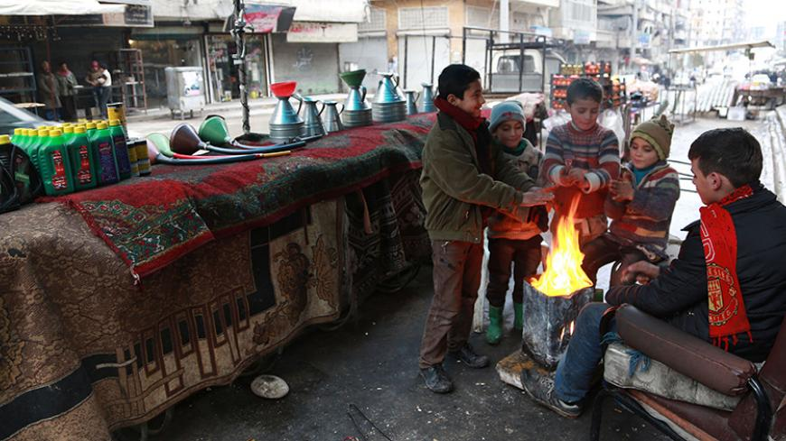 Children warm themselves next to an open fire beside fuel barrels, engine oil and accessories displayed for sale in Aleppo January 13, 2015. Residents of Kafr Hamra, a town in the rural Aleppo countryside, refine crude oil in makeshift cottage refineries in warehouses and backyards for heating, operating bakeries and even running cars, just like most locals across rebel-held areas of Syria. The state no longer pumps gasoline to areas in rebel hands, and civilians have resorted to buying crude oil from armed