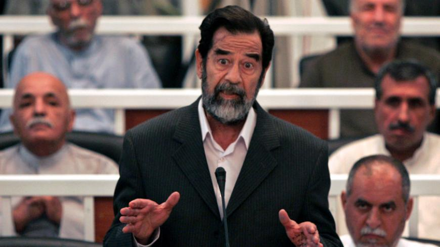 Saddam Hussein speaks to the Presiding Judge Rizgur Ameen Hana Al-Saedi as his trial begins in a heavily fortified courthouse in Baghdad's Green Zone October 19, 2005. Behind Saddam on his immediate right is Awad Hamad al-Badar, while in the second row are (R to L) Mizhar Abdullah Ruwayyid and Taha Yassin Ramadan. In the third row are (R to L) Ali Dayim Ali, Mohammed Azawi. A defiant Saddam went on trial on Wednesday for crimes against humanity over the killing of more than 140 Shi'ites more than two decade