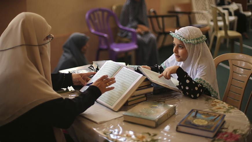 A Palestinian girl recites Koran to her teacher during a Koran memorization lesson on the first day of the holy fasting month of Ramadan at a mosque in Gaza City June 29, 2014.REUTERS/Mohammed Salem (GAZA - Tags: RELIGION SOCIETY EDUCATION) - RTR3W9WR