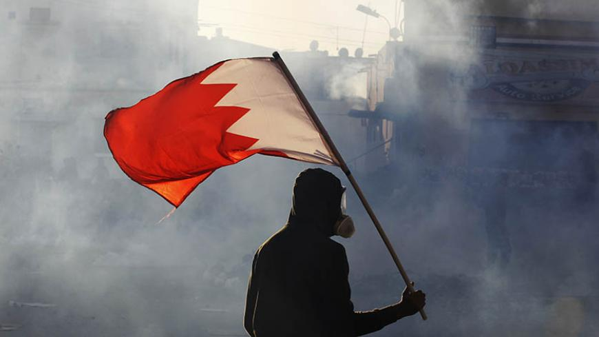 A protester carries a Bahraini flag as they clash with riot police in the village of Bilad Al Qadeem south of Manama, February 6, 2015.  Protesters clashed with riot police demanding for the release of Bahraini opposition leader Sheik Ali Salman. Sheik Salman, head of the al-Wefaq Islamic Society was arrested on December 28, 2014 after leading a protest rally against elections in November which his party boycotted.  REUTERS/ Hamad I Mohammed (BAHRAIN). - Tags: POLITICS CIVIL UNREST) - RTR4OIT8