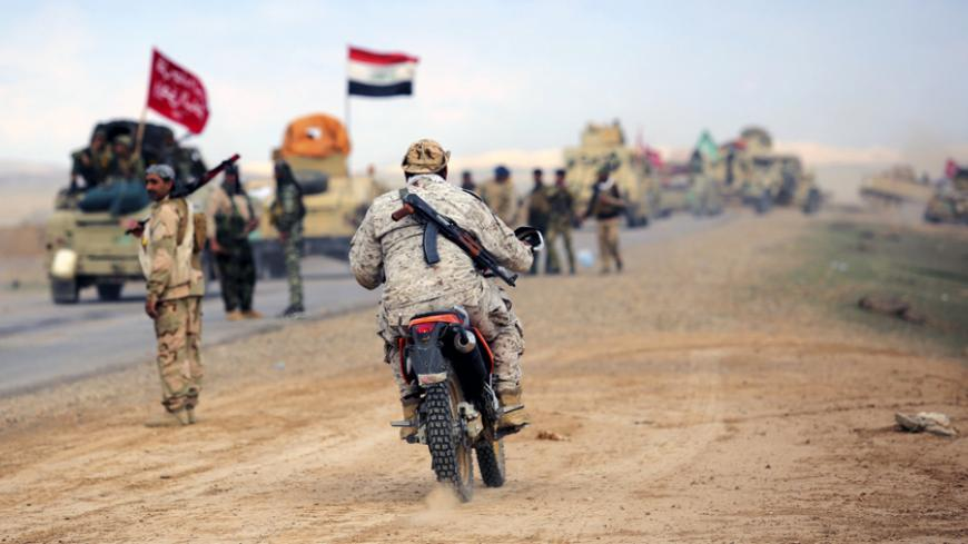 A Shi'ite fighter rides a motorbike in the town of Hamrin in Salahuddin province March 5, 2015. As Iraqi forces close in, Tikrit's few remaining civilians are cutting up white clothes and fabric to make flags of surrender, fearing their Shi'ite liberators more than the Islamic State militants occupying the Sunni city.  REUTERS/Stringer (IRAQ - Tags: POLITICS CIVIL UNREST CONFLICT) - RTR4S8Q5