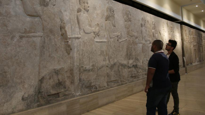 Visitors look at Assyrian mural sculptures from Khorsabad, at the Iraqi National Museum in Baghdad March 8, 2015. Islamic State militants have desecrated another ancient Iraqi capital, the government said on March 11, 2015, razing parts of the 2,700-year-old city of Khorsabad famed for its colossal statues of human-headed winged bulls.  Picture taken March 8, 2015.   REUTERS/Khalid al-Mousily (IRAQ - Tags: SOCIETY CIVIL UNREST) - RTR4SZAO