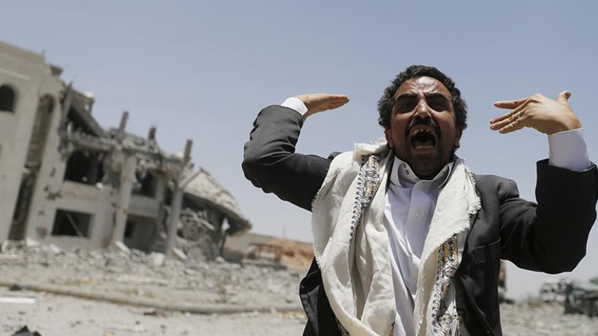A Houthi militant reacts at the yard of the residence of the military commander of the Houthi militant group, Abdullah Yahya al Hakim, after an air strike destroyed it, in Sanaa April 28, 2015. Saudi-led aircraft pounded Iran-allied Houthi militiamen and rebel army units on Monday, dashing hopes for a pause in fighting to let aid in as relief officials warned of a catastrophic humanitarian crisis. REUTERS/Khaled Abdullah - RTX1AM8S