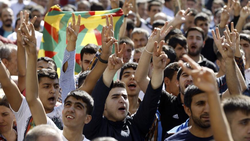 Kurdish demonstrators gesture as Selahattin Demirtas, co-chair of the HDP, Turkey's leading Kurdish party, addresses a crowd in Diyarbakir October 9, 2014. A three-week battle for the Syrian border town of Kobani has also led to the worst streets clashes in years between police and Kurdish protesters across the frontier in southeast Turkey. In Diyarbakir, Turkey's biggest Kurdish city, five people were killed in clashes on Monday and Tuesday between Islamist groups and PKK supporters, a senior police office