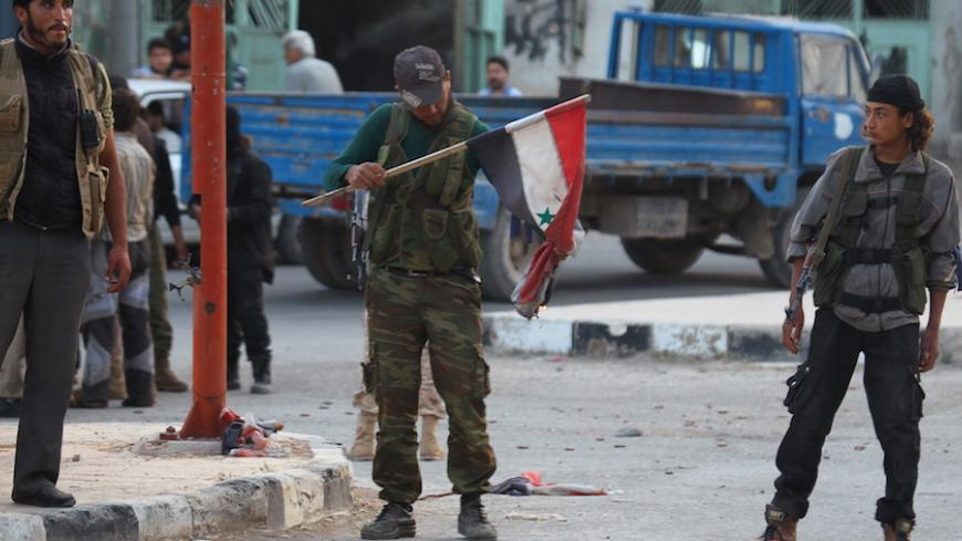 A member of al Qaeda's Nusra Front burn a Syrian national flag in the town of the northwestern city of Ariha, after a coalition of insurgent groups seized the area in Idlib province May 29, 2015. The Syrian army has pulled back from the northwestern city of Ariha after a coalition of insurgent groups seized the last city in Idlib province in northwestern Syria near the Turkish border that was still held by the government. A coalition of rebel groups called Jaish al Fateh, or Conquest Army, said it had taken