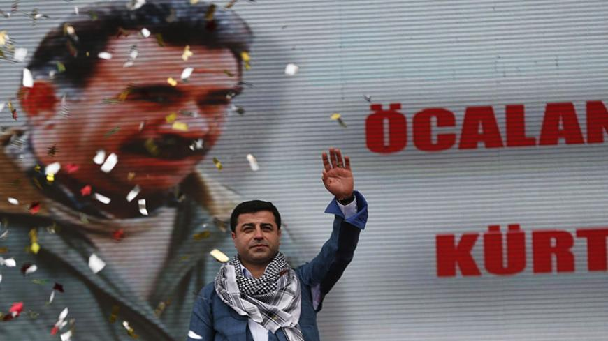 Selahattin Demirtas, co-chairman of the pro-Kurdish Peace and Democracy Party, greets his supporters during a rally to celebrate the spring festival of Newroz in Istanbul March 17, 2013. A picture of imprisoned PKK leader Abdullah Ocalan is seen in the background. REUTERS/Murad Sezer (TURKEY - Tags: POLITICS CIVIL UNREST) - RTR3F4BY