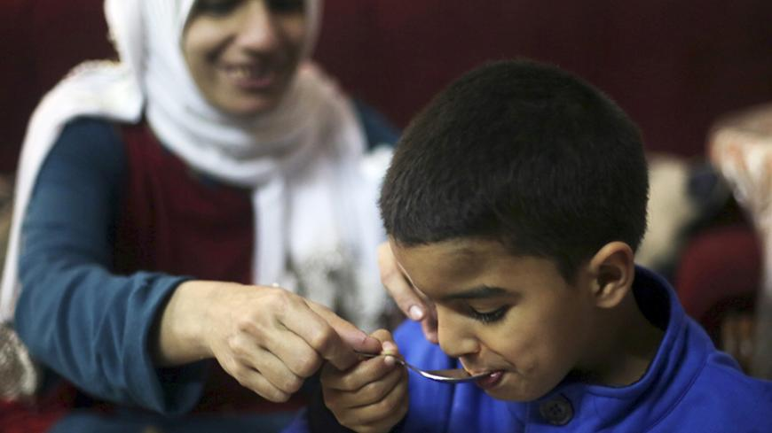 Sherien Fathy, a blind 32-year-old mother of two, feeds her son Yehia at her home in Cairo March 5, 2014. Sherien, a graduate of the College of Arts? Arabic department who works as a specialist manager at the General Petroleum Corporation, hopes the government will do more to help disabled people to find jobs and contribute to the economy. Sherien is married to lawyer Khaled Hanafy, who is also blind. On March 8 activists around the globe celebrate International Women's Day, which dates back to the beginnin