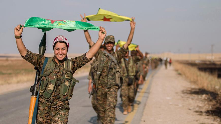 Kurdish fighters gesture while carrying their parties' flags in Tel Abyad of Raqqa governorate after they said they took control of the area June 15, 2015. Syrian Kurdish-led forces said they had captured a town at the Turkish border from Islamic State on Monday, driving it away from the frontier in an advance backed by U.S.-led air strikes that has thrust deep into the jihadists' Syria stronghold. The capture of Tel Abyad by the Kurdish YPG and smaller Syrian rebel groups means the Syrian Kurds effectively
