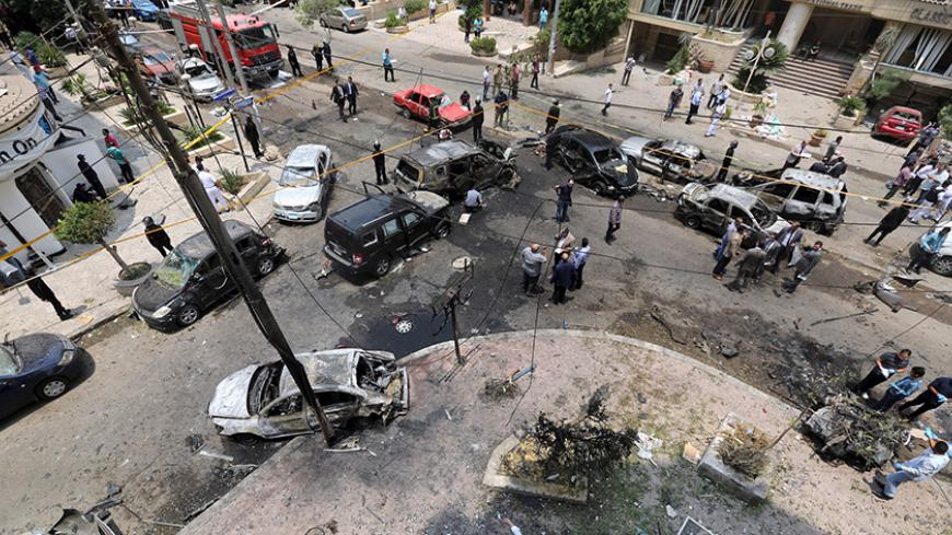 A view shows burnt cars at the site of a car bomb attacked the convoy of Egyptian public prosecutor Hisham Barakat near his house at Heliopolis district in Cairo, Egypt, June 29, 2015. Barakat was injured when a car bomb struck his convoy as it was leaving his home in Cairo on Monday, in a high-profile attack against the judiciary, security and judicial sources said. REUTERS/Mohamed Abd El Ghany - RTX1I937