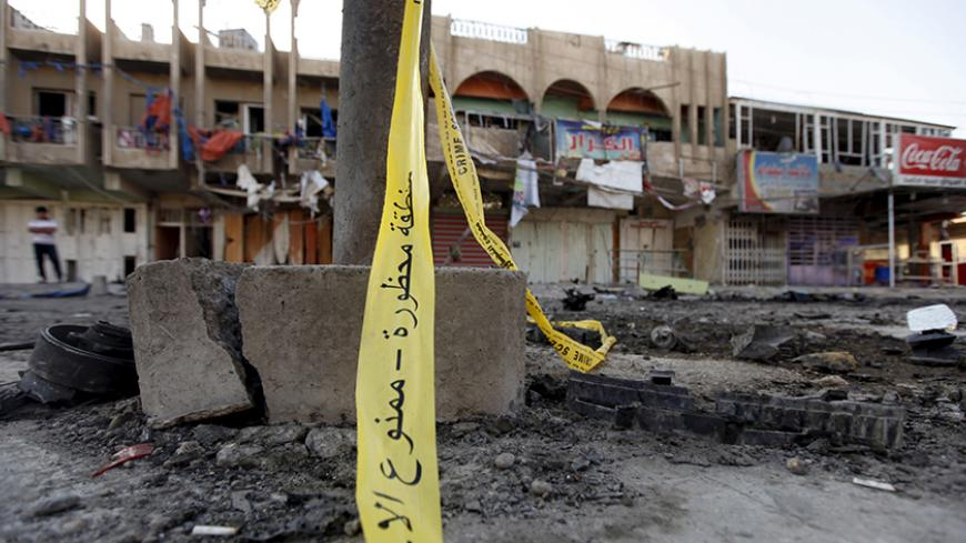 The site of a bomb attack is seen in Baghdad July 23, 2015. A car bomb exploded in a crowded marketplace in a mainly Shi'ite Muslim district of the Iraqi capital on Wednesday, killing at least 20 people, police and medical sources said.  REUTERS/Ahmed Saad - RTX1LFX6