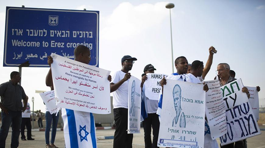 Demonstrators hold placards during aprotest calling for the release of Avraham Mengisto at the Erez Crossing in southern Israel, near the Gaza Strip August 27, 2015. Two Israeli citizens, one of them Mengisto, are being held by Hamas in the Gaza Strip, Prime Minister Benjamin Netanyahu said last month, a situation that could lead to demands for a prisoner exchange between Israel and the Islamist militant group. Hamas, the Palestinian enclave's dominant faction, declined to confirm or deny it had the captive
