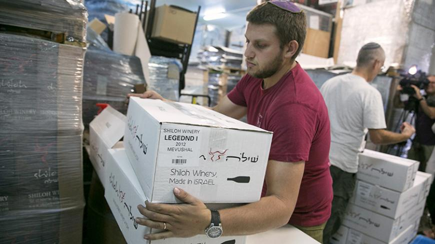 "A worker carries boxes containing wine bottles for export at Shiloh Wineries, north of the West Bank city of Ramallah November 8, 2015. Few issues have caused more friction between Israel and the European Union than EU plans to impose labeling on goods produced in Jewish settlements on occupied land. And if Israel is right about the timing, the tensions could get worse."" Shiloh Wineries, which exports half of the more than 100,000 bottles of wine it produces annually, built its business around its West Bank"