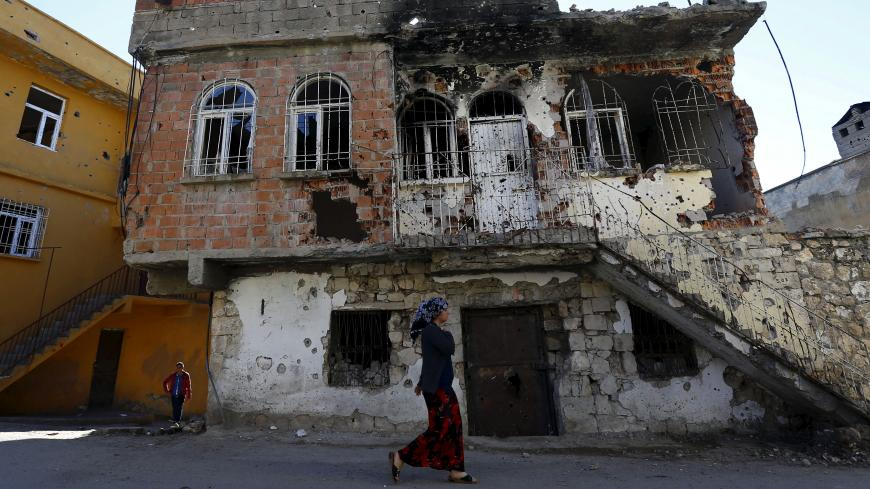 A woman walks past a building which was damaged during the security operations and clashes between Turkish security forces and Kurdish militants, in the southeastern town of Silvan in Diyarbakir province, Turkey, December 7, 2015. Picture taken December 7, 2015. To match Insight TURKEY-POLITICS/KURDS REUTERS/Murad Sezer - RTX1ZB0S