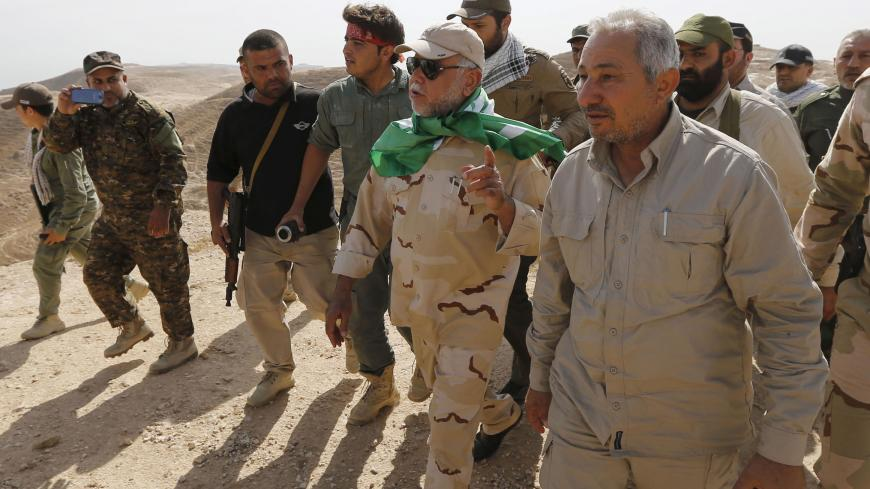 Head of the Badr Organisation Hadi al-Amiri (C) walks with Shi'ite fighters in Makhoul mountains, north of Baiji, October 17, 2015. Iraqi forces and Shi'ite militia fighters recaptured most of the country's largest oil refinery from Islamic State militants on Thursday, security officials said. The report could not be independently confirmed because it is too dangerous for journalists to enter the battle zone around the refinery near the town of Baiji, about 190 km (120 miles) north of Baghdad. REUTERS/Thaie
