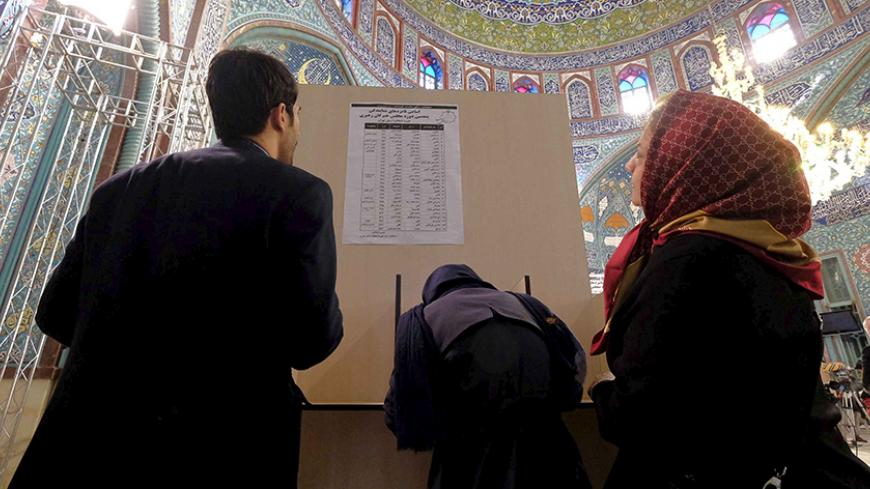 Iranians look at a list of candidates' names during elections for the parliament and Assembly of Experts, which has the power to appoint and dismiss the supreme leader, at a polling station in Tehran February 26, 2016. REUTERS/Raheb Homavandi/TIMA  ATTENTION EDITORS - THIS IMAGE WAS PROVIDED BY A THIRD PARTY. FOR EDITORIAL USE ONLY. - RTX28NK7