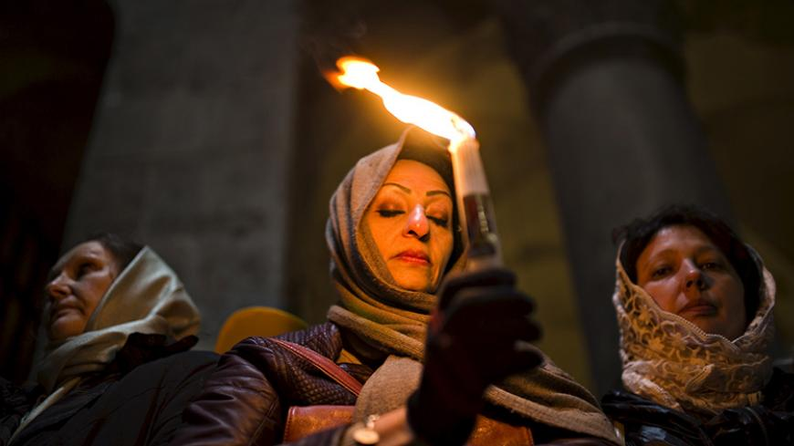 A Christian worshipper holds a candle, before Easter Sunday mass procession inside the Church of the Holy Sepulchre in Jerusalem's old city April 12, 2015. REUTERS/Amir Cohen - RTR4X06K