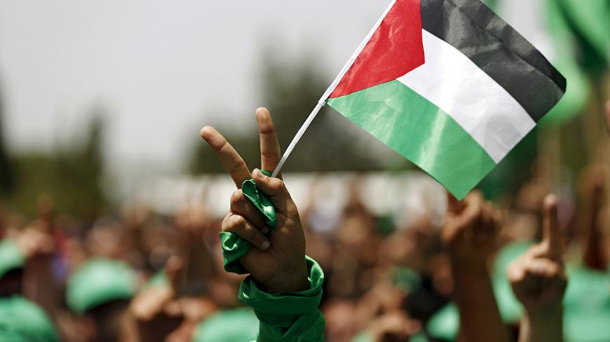 A student supporting Hamas holds a Palestinian flag in a rally during an election campaign for the student council at the Birzeit University in the West Bank city of Ramallah April 26, 2016. REUTERS/Mohamad Torokman  - RTX2BOVO