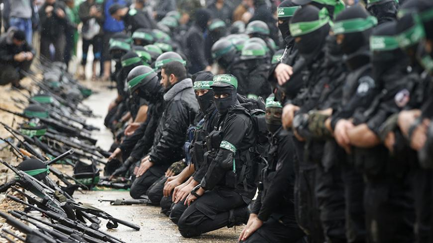 Palestinian members of al-Qassam Brigades, the armed wing of the Hamas movement, pray before a military parade marking the 27th anniversary of Hamas' founding, in Gaza City December 14, 2014.  REUTERS/Mohammed Salem (GAZA - Tags: POLITICS MILITARY ANNIVERSARY RELIGION) - RTR4HY0R